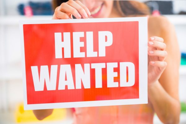 Midsection of smiling female owner holding help wanted sign in retail store